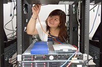 Student working with computer servers in a server room.
